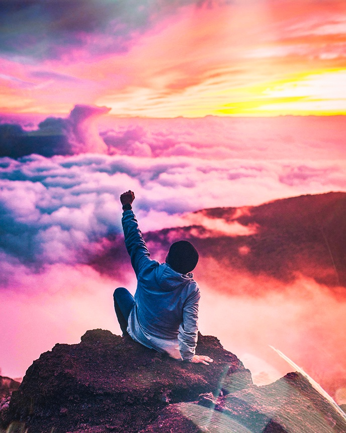 Man on top of a mountain above clouds